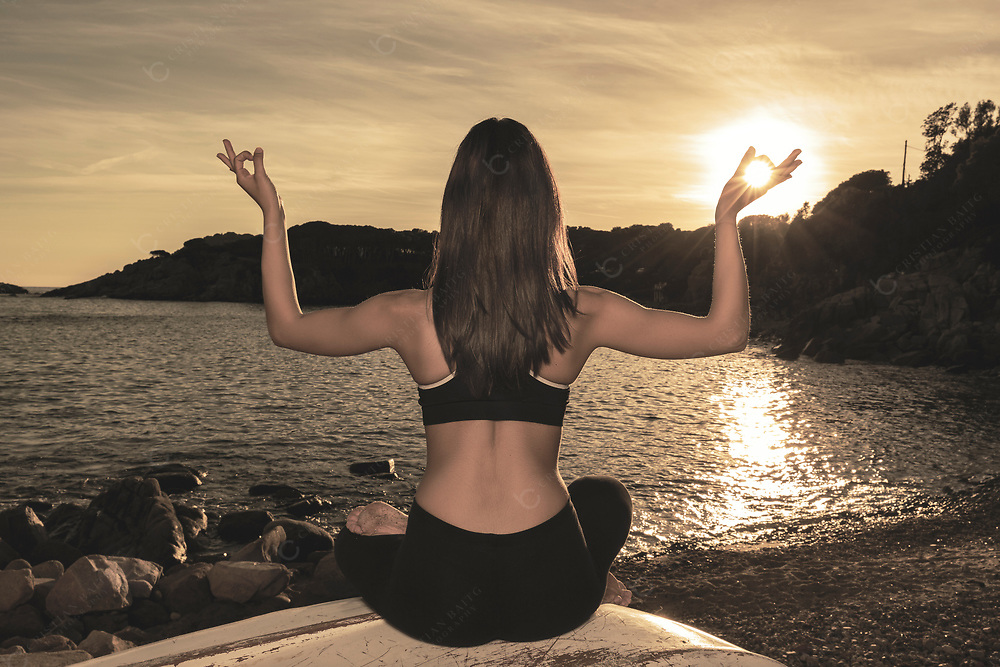 Woman in yoga lotus pose the sea at sunset