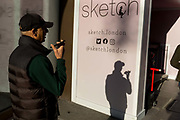 A man speaks into his phone using the speakerphone feature, in a sunny corner next to Sketch, a gastro-gallery on Conduit Street, on 20th January 2020, in London, England.