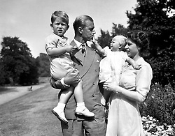 Princess Anne in the arms of Princess Elizabeth, with the Duke of Edinburgh, holding Prince Charles, in the grounds of Clarence House, their London residence.