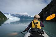 Woman kayaking on Aialik Bay towards Aialik Glacier, Kenai Fjords National Park, Alaska