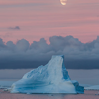 'Moonrise Over Midnight Glow' – Grandidier Channel, Antarctica<br /> After hosting the Ukrainian scientist from the Akademik Vernadsky Station for a BBQ aboard our vessel, we turned north and sailed through the Grandidier Channel.  At around midnight, the     afterglow cast soft pink light on the water and icebergs just as the moon was rising.