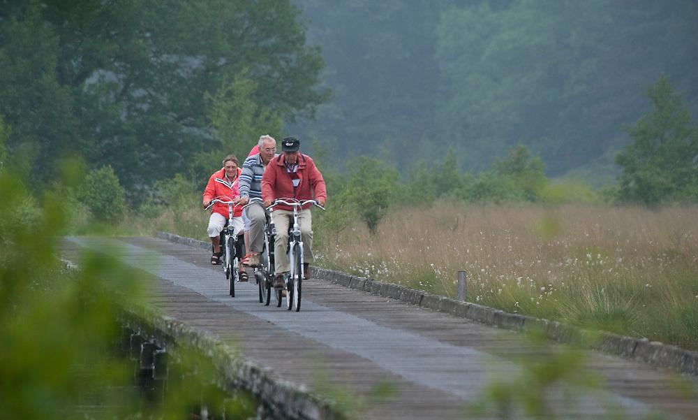 Nederland, Schoonloo, 30 juni 2010.Drents natuuurgebied met oudere mensen op de fiets.Foto (c)  Michiel Wijnbergh