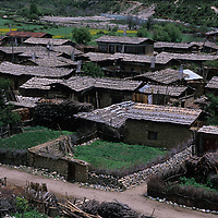 CHINA, TIBET. Village east of Nyingchi, where stone walls surround potato fields and stones hold shingles onto roofs.