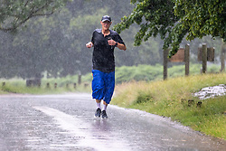 Licensed to London News Pictures. 12/07/2021. London, UK. A runner gets caught in torrential rain in Richmond Park, southwest London this afternoon with roads and pavements becoming quickly flooded as the Met Office issue yellow weather warnings for heavy rain and thunderstorms which may cause disruption to travel and flooding. However, sunshine and warm weather is predicted for the rest of the week with highs of 26c for the weekend.. Photo credit: Alex Lentati/LNP