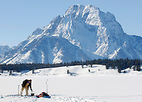 A fisherman his line while ice fishing New Year's Day on Jackson Lake in Grand Teton National Park.