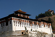 The towering white painted stone walls of Paro Dzong, Rinchen Pung Dzong, Rinpung Dzong, Fortress on a heap of Jewels. The National Museum of Bhutan in the round watchtower can be seen above the Dzong.   Paro, Druk Yul, Bhutan. 12 November 2007.
