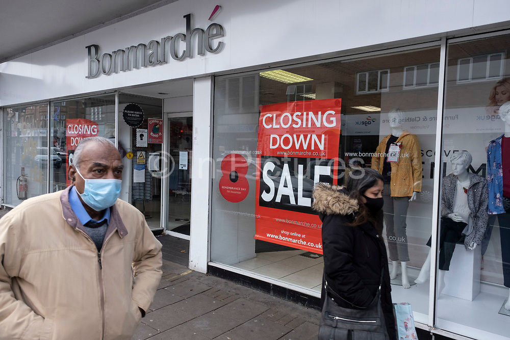 Some shops like Bonmarche advertise sales although are closing down as the second national lockdown continues with just over a week before the new tier system begins, and people, many of whom are wearing face masks, come to Kings Heath High Street, as all non-essential shops are closed while some remain trading on 23rd November 2020 in Birmingham, United Kingdom. The new national lockdown is a huge blow to the economy and for individual businesses who were already struggling with only offering limited services.