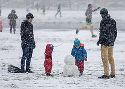 © Licensed to London News Pictures. 24/01/2021. London, UK. A family build a snowman in the snow on Wimbledon Common. Members of the public go out on Wimbledon Common in blizzard like conditions as the temperature dropped to lows of -5 in South West London this morning. A chilly day ahead is forecast for the South East with the Met Office issuing a yellow weather warning for snow today with disruption to travel as the cold weather continues. Photo credit: Alex Lentati/LNP