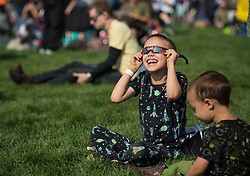 A boy watches the total solar eclipse through protective glasses in Madras, Oregon on Monday, Aug. 21, 2017. A total solar eclipse swept across a narrow portion of the contiguous United States from Lincoln Beach, Oregon to Charleston, South Carolina. A partial solar eclipse was visible across the entire North American continent along with parts of South America, Africa, and Europe.  Photo Credit: (NASA/Aubrey Gemignani)