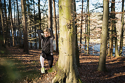 Fit woman stretching on fitness trail in nature