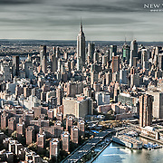 View of midtown Manhattan from above the East River with the Empire State Building front and center again.