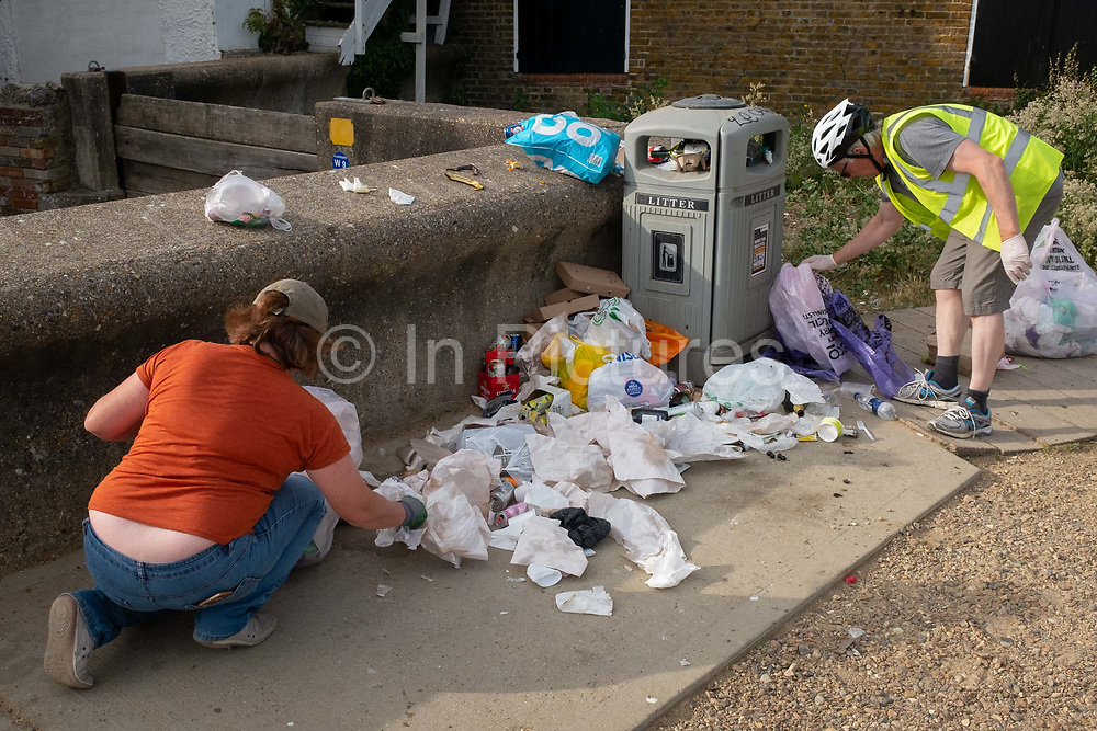 The morning after Saturday night crowds of young peoples nightlife beach parties, their litter and rubbish from the night before stretches across the coastal paths and shingle, local volunteers pick up and bags up piles of litter along the sea wall, on 19th July 2020, in Whitstable, Kent, England.  The volunteers and a council cleaner come every morning to clean-up the mess left by others which, they say, has got worse during the Coronavirus pandemic lockdown and now, the slow easing of health guidelines.