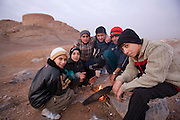 Boys warm themselves over an impromptu fire at dusk near the abandoned Zoroastrian towers of silence in Yazd, Iran. Zoroastrians brought their dead to towers of silence to be eaten by birds before the practice was outlawed by the Iranian government.  The bodies of the dead were considered unclean by Zoroastrians and so corpses were put atop the towers (often hilltops) so that the earth would not be polluted by the remains. Today Zoroastrians in the community are buried in a nearby cemetary, although placed so that the body does not touch the earth.