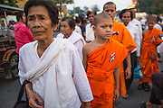 """29 JANUARY 2013 - PHNOM PENH, CAMBODIA:  Mourners in white and Cambodian Buddhist monks make their way to the Royal Palace in Phnom Penh to mourn for late Cambodian King Norodom Sihanouk. Sihanouk (31 October 1922- 15 October 2012) was the King of Cambodia from 1941 to 1955 and again from 1993 to 2004. He was the effective ruler of Cambodia from 1953 to 1970. After his second abdication in 2004, he was given the honorific of """"The King-Father of Cambodia."""" Sihanouk held so many positions since 1941 that the Guinness Book of World Records identifies him as the politician who has served the world's greatest variety of political offices. These included two terms as king, two as sovereign prince, one as president, two as prime minister, as well as numerous positions as leader of various governments-in-exile. He served as puppet head of state for the Khmer Rouge government in 1975-1976. Most of these positions were only honorific, including the last position as constitutional king of Cambodia. Sihanouk's actual period of effective rule over Cambodia was from 9 November 1953, when Cambodia gained its independence from France, until 18 March 1970, when General Lon Nol and the National Assembly deposed him. Upon his final abdication, the Cambodian throne council appointed Norodom Sihamoni, one of Sihanouk's sons, as the new king. Sihanouk died in Beijing, China, where he was receiving medical care, on Oct. 15, 2012. His cremation is scheduled to take place on Feb. 4, 2013. Over a million people are expected to attend the service.      PHOTO BY JACK KURTZ"""