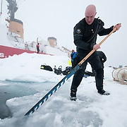 Shawn Harper cuts a hole in the ice for a diving. Arctic Ocean