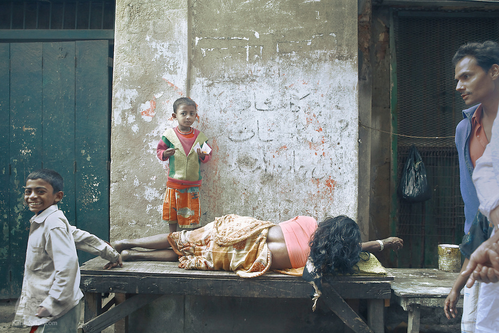 A mother sleeps on a wooden table while her children play in the street. The seemingly universal and severity of poverty in Kolkata can be overwhelming for many western visitors.