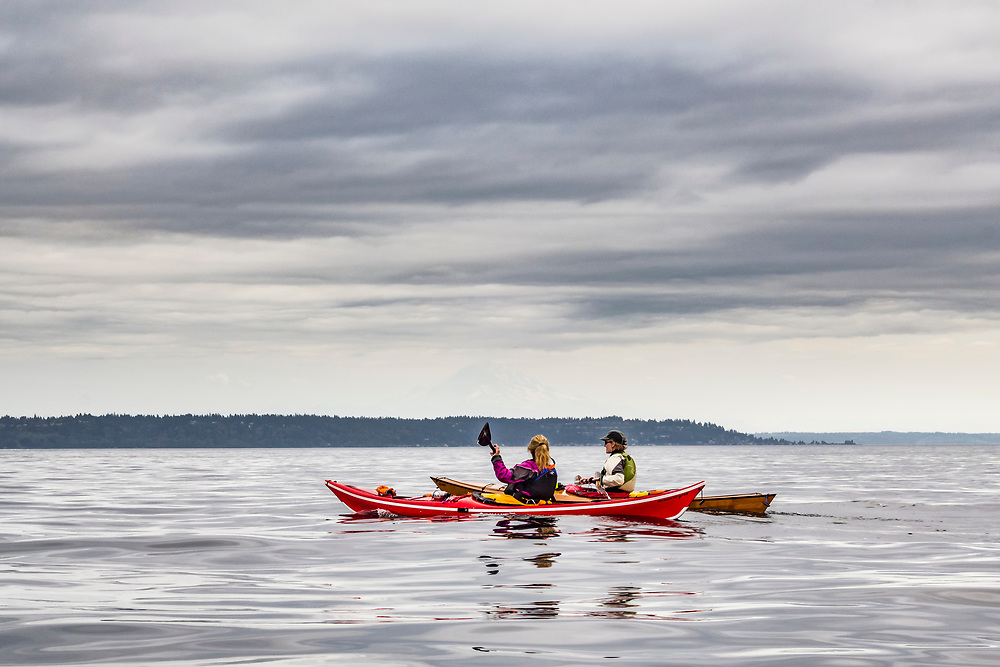 Two women out in the Salish Sea making a crossing from Blake Island to West Seattle with Mount Rainier barely visible in the distance. Puget Sound, Washington, USA.