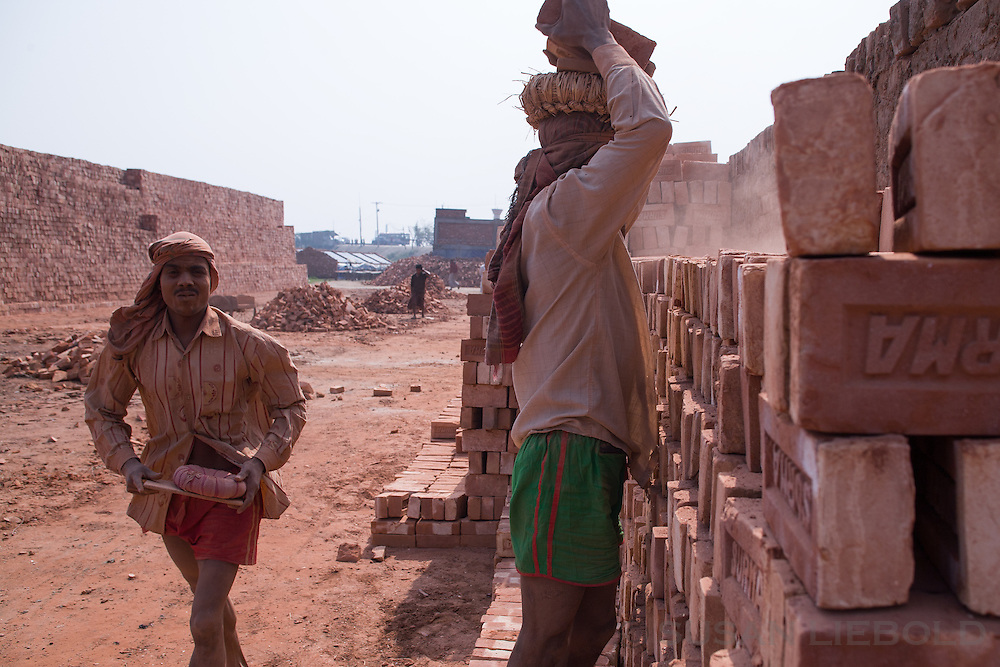 Men carry stacks of bricks on their heads to transport to another location at the factory, Bangladesh.