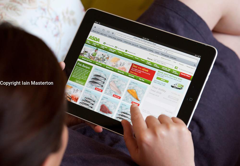 Woman shopping at online Asda supermarket store using an iPad tablet computer