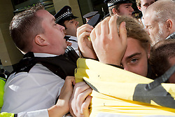 © Licensed to London News Pictures. 15/10/2011. LONDON, UK. A protester covers his face as Police force protesters away from Paternoster square.  Protesters attempted to occupy the London Stock Exchange today (Saturday) in solidarity with protests in New York's financial district. Photo credit : James Gourley/LNP