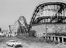 Abandoned car and wooden roller coaster in Coney Island, NY