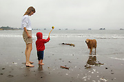 A woman and toddler play with a golden retriever on the beach near Crescent City, California