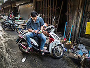 14 DECEMBER 2015 - BANGKOK, THAILAND:  A man sits on his motor scooter and checks his smart phone in Bang Chak Market. Many of the shops in the market are already shuttered. The market closes permanently on Dec 31, 2015. The Bang Chak Market serves the community around Sois 91-97 on Sukhumvit Road in the Bangkok suburbs. About half of the market has been torn down. Bangkok city authorities put up notices in late November that the market would be closed by January 1, 2016 and redevelopment would start shortly after that. Market vendors said condominiums are being built on the land.      PHOTO BY JACK KURTZ