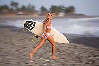 Young woman walking on beach after surfing. Mexico.