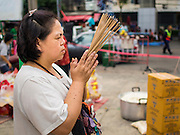 """07 AUGUST 2014 - BANGKOK, THAILAND:  A woman prays at Pek Leng Keng Mangkorn Khiew Shrine. Thousands of people lined up for food distribution at the Pek Leng Keng Mangkorn Khiew Shrine in the Khlong Toei section of Bangkok Thursday. Khlong Toei is one of the poorest sections of Bangkok. The seventh month of the Chinese Lunar calendar is called """"Ghost Month"""" during which ghosts and spirits, including those of the deceased ancestors, come out from the lower realm. It is common for Chinese people to make merit during the month by burning """"hell money"""" and presenting food to the ghosts. At Chinese temples in Thailand, it is also customary to give food to the poorer people in the community.     PHOTO BY JACK KURTZ"""