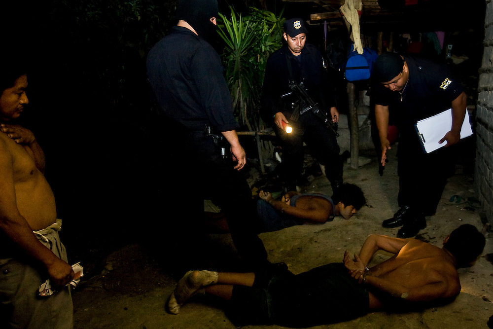 A suspected thief and gang member is identified by an investigator during a midnight raid in the country side near San  Salvador.  Constant police pressure in El Salvador is pushing many Maras to the country side where they find it easy to bring disaffected local youths into the gang.