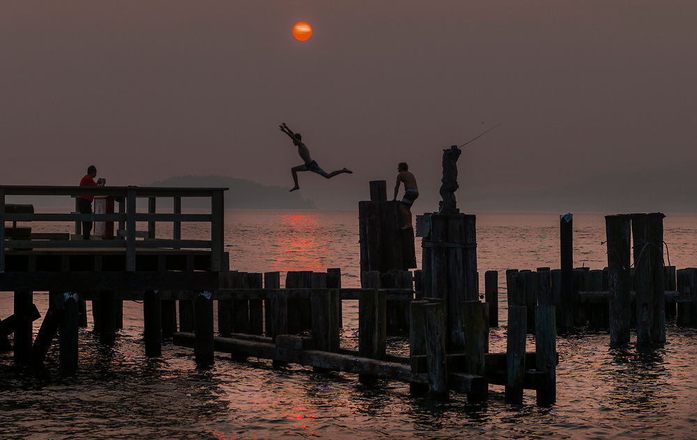 An evening swim from a pier as the sunset is diffused by smoke from forest fires burning north of Sechelt, BC  (2018)
