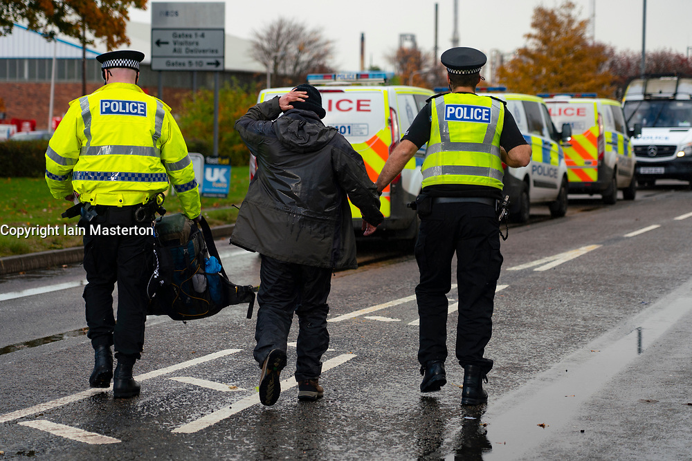 Grangemouth, Scotland, UK. 23 October 2020. Extinction Rebellion climate change protesters block entrance to INEOS headquarters at Grangemouth. Protesters have locked themselves together with chain and have parked a yacht in the road blocking access. Police have closed Inchyra Road. Pictured; Protester is arrested and taken into custody. Iain Masterton/Alamy Live News