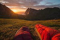 Watching colorful summer sunset over Bunes beach from sleeping bags, Moskenesøy, Lofoten Islands, Norway