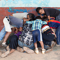 Boys fascinated by someone's mobile phone, huddle together outside their school.