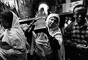 Ethipian pilgrims carry a cross down the Via Dolorosa during the Easter celebrations. The Ethiopian Orthodox Monastery built on the roof of the Holy Sepulchre Jerusalem Israel. The Ethiopians have no property in the Hly Sepulchre only access rights and have a small monastery Deir es-Sultan on the roof of a small annex.