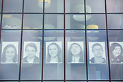 """Portraits of Skyview students are seen in the windows of the Vancouver Library Thursday May 17, 2018. Skyview photography students created the public art project called  """"Inside Out""""  The portraits will dominate the streetscape outside the library for a month. (Photo by Natalie Behring for the Columbian)"""