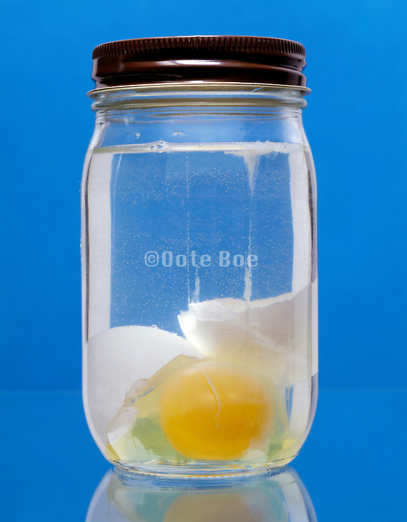 A glass jar with water and a broken egg.