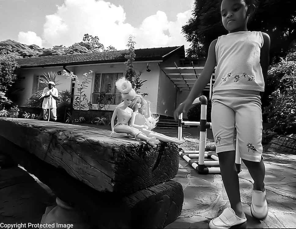 Connie Pietersen, 7, plays with her barbie dolls in her yard in Houghton, Johannesburg.  In the background is the family's gardner.  With her father in the cell phone business, Connie's family is part of the growing black elite in post-apartheid South Africa.  They live in a large house in one of the most expensive neighborhoods in Johannesburg, have multiple servants and both parents drive BMWs.
