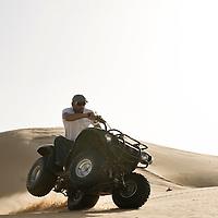 Al-Ain (Abu Dhabi), United Arab Emirates 04 April 2009.A man drives a cuatri in the  desert of AL Ain..PHOTO: EZEQUIEL SCAGNETTI