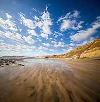 Vertical Panorama (vertorama) of the beach at Compton with cumulus clouds Reflected on the wet sand at low tide.