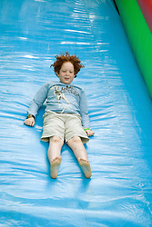 Boy enjoying the big inflatable slide at a Parklife summer activities event,