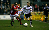 Arturo Lupoli (right, white) of Derby County attacks against Shaun Pejic (red, left) of Wrexham