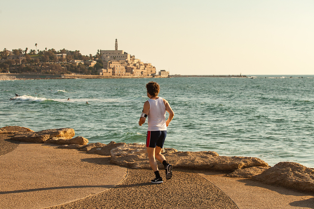 The Old City of Jaffa and the Mediterranean Sea provide the backdrop, as man is seen jogging at the promenade of Charles Clore Park, in Tel Aviv's Neve Tzedek neighborhood