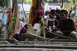 June 16, 2018 - Lhokseumawe, Indonesia - A couple seen reading the Quran to one of their relative during the pilgrimage..Muslims seen with their relatives' grave during a pilgrimage at the public cemetery in Lhokseumawe City. Most Muslims in Aceh already made the last grave pilgrimage before entering the holy month of Ramadan and on the day of Eid al-Fitr, to pray for the families of those who have died. (Credit Image: © Maskur Has/SOPA Images via ZUMA Wire)
