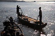 FISHERMEN MEKONG RIVER. South East Asia, Cambodia, Phnom Penh, Mekong River. The Cham fisher people live in various desolated villages along the banks of the Mekong and Tonle Sap rivers. The fisher families live like river gypsy nomads, working and living on their boats, sleeping under a sprung bamboo frame, all their worldly goods stored below deck. They live in extended families, with numerous boats, together for safety. Their diet is rice, vegetables and fish. Their sleek wooden boats are powered by petrol outboard motors with batteries or generators to supply lighting at night. Their fishing technique is laying nets twice or three times per day, which are weighted well below the surface, using old paint aerosal canisters as buoyant floaters, hanging just beneath the surface. These particular fisher families, living at the junction of the Mekong and Tonle Sap rivers, overlooked by Phnom Penh, sell their catch at the Vietnamese market, on the banks of the river. Their life and fortunes are controlled by the cycle of the river. As the river levels drop, so the quantity of fish decreases, until after the heavy floods of the monsoon they fill the river again. They are poor traditional Muslims, marginalised from mainstream society, living a third world life in the immmediate shadow of the first world. The Cham, originally a people of an ancient kingdom called Champa, are a small and disenfranchised community who were disinherited of their land. They are a socially important ethnic group in Cambodia, numbering close to 300,000. The Cham people, live in some 400 villages across Kampong Chnang and Kampong Cham provinces. Their religion is Muslim and their language belongs to the Malayo-Polynesian family. Their livelihoods are as diverse as rice farming, cattle trading, hunting and fishing.///Cham fishing boats silhouetted against the waters of the Mekong and Tonle Sap rivers