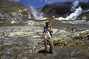 Tourist, wearing the compulsory gas mask, standing in the main crater of White Island. The main crater of this active volcanic island is accessible for the daring tourists when there is no imminent major activity. However, when you take the boats ex Whakatane, you do so at your own risk …