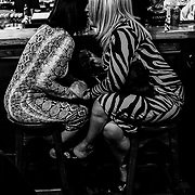 """Ladies chat amidst traditional Nationalist songs sung at the Castle Bar during """"Rebel Sundays"""" on Waterloo Street. Northern Ireland, September 2019"""