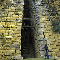 Peruvian archaeologist Dr. Peter Lerche examines a narrow entrance between the imposing fortress walls at Kuelap, a stronghold of the pre-Incan, Chachapoyan culture.