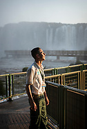 Iguazu Falls, Brazil - March 27, 2019: Saymon Jesus, age 19, smiles in the mist and sunlight at closing time at Iguazú National Park, where he is an employee, in Brazil.
