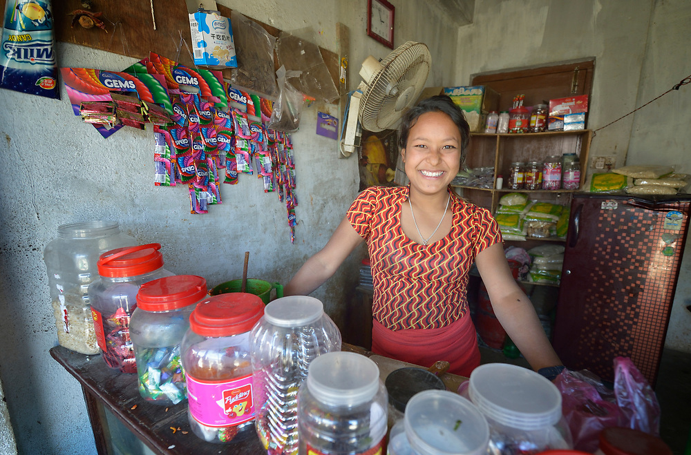 """Saru Shrestha poses in her small shop in Sanogoan, Nepal, where she earns money to support her family in the wake of the April 2015 earthquake that ravaged Nepal. <br /> <br /> The Newar community where she lives was particularly hard hit, but it has been helped by the Lutheran World Federation, a member of the ACT Alliance. The ACT Alliance has provided blankets, tents, and livelihood assistance, including a cash grant to help Shrestha jump start her business, and is helping villagers form the tens of thousands of cement blocks they will need to construct permanent housing. <br /> <br /> Born into a family of 10, Shrestha had to leave school after the earthquake to help care for her younger brothers and sisters. Using the small grant, Shrestha established a shop selling tea, snacks and sweets. """"At first it was hard, especially arguing with people who buy things on credit. But I feel less shy now,"""" said Shrestha, who uses most of the income to pay for school fees for her siblings. Some of it she sets apart. """"My dream is to open a second shop, selling cosmetics,"""" said the young entrepreneur."""